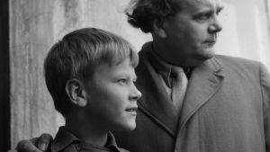 Nuori poika ja hänen isänsä seisovat kuvasta oikealle katsellen, isän käsi pojan olalla. Kuvanottohetki 50-60-lukujen taite.