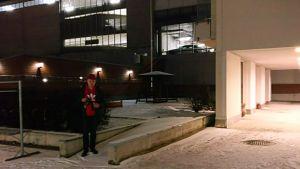 mies seisoo ulkona rakennuksen edessä