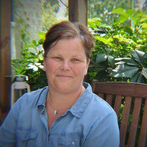 kvinna sitter i sin trädgård