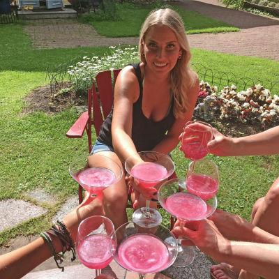 Hanna kilistää ystävien kanssa pinkeillä drinkeillä.