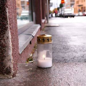 Ljus brinner utanför porten där den unga kvinnan bragdes om livet.