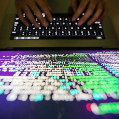 På bilden syns en datorskärm med massa kodspråk. Bilden är tagen uppifrån och man ser hur två händer skriver på tangentbordet.