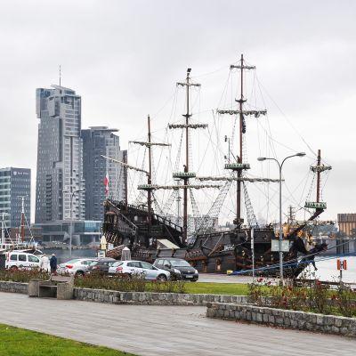 Det svarta piratskeppet Dragon ligger vid kajen i Gdynia, med gräsmatta och bilar framför och höghus i bakgrunden.