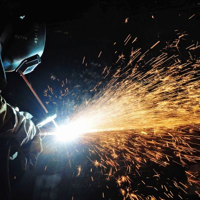 Mies hitsaa öljynporauslautalla Kiinan Qingdaossa.