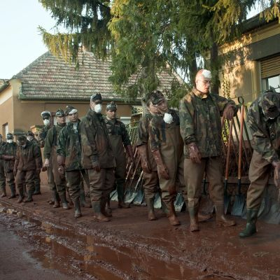 Unkarilaisia sotilaita jonossa. Sotilaat värjäytyneet myrkkyliejusta punaisiksi.