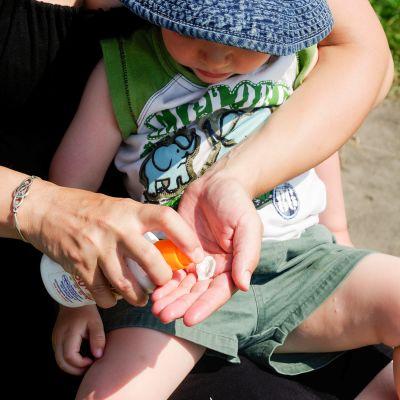 Äiti laittaa aurinkorasvaa lapselleen.
