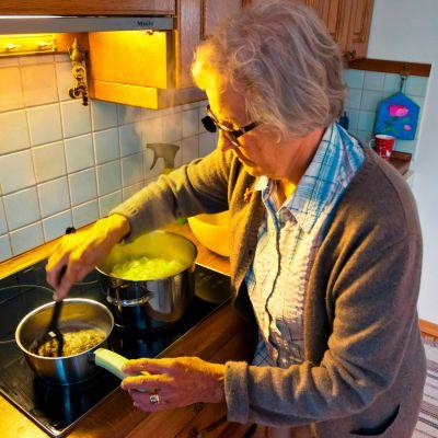 Eläkeläinen valmistaa ruokaa kotonaan.