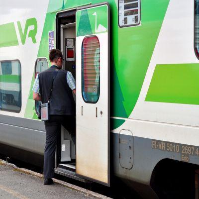Konduktööri nousemassa junanvaunuun.