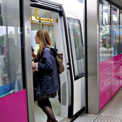 Ihmisiä nousemassa metrojunan kyytiin Kastrupin lentokentällä.