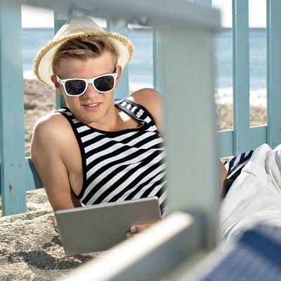 Nuori poika katselee tablettia rannalla.