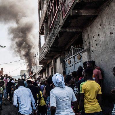 Asukkaat katselivat kun savu nousi pudonneesta lentokoneesta Gomassa 24. marraskuuta.