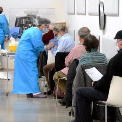 Ihmiset jonottavat rokotukseen Italiassa