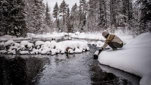 Tova Christoffersson hämtar vatten ur en bäck.