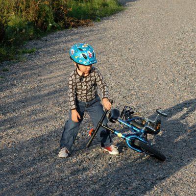 Lapsi nostaa kaatunutta polkupyörää soratiellä.