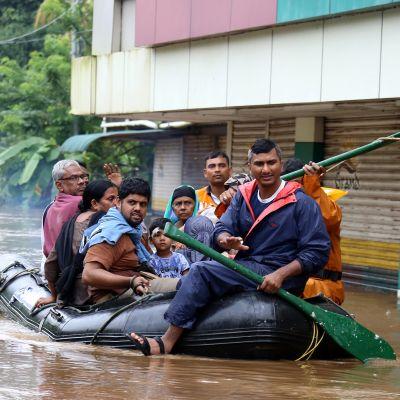 Ihmisiä kumiveneessä Kochin kaupungissa Keralassa.