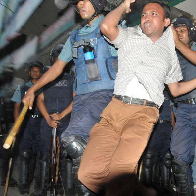 Poliisi pidättä mielenosoittajia Dhakaassa marraskuussa 2013.