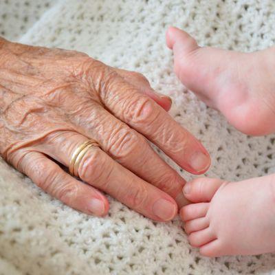 Vanhan naisen käsi koskettaa vauvan jalkoja.