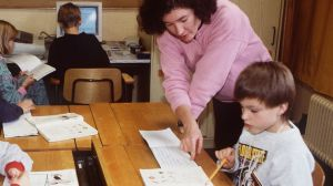 Opettaja ohjaamassa oppilaita harjoitustehtävien tekemisessä 1990-luvulla. Taustalla oppilaita tietokoneen ääressä