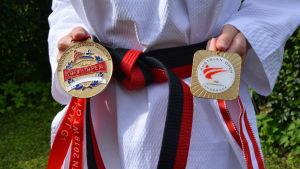 En kvinna i taekwondodräkt håller i två medaljer framför ett svartrött bälte.