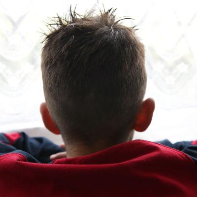 Pojke fotograferad bakifrån. Hans huvud och axlar syns och han är klädd i en långärmad tröja.