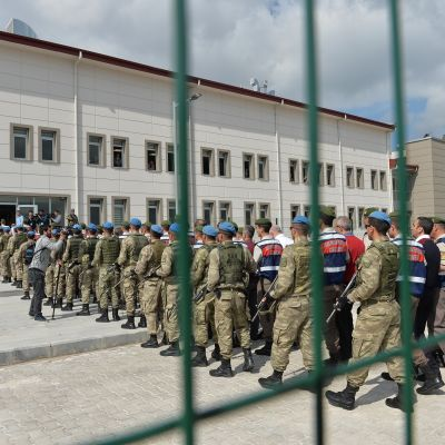 Kaltereiden ympäröimällä pihalla kulkee jonossa syytettyjä, ja vieressä kulkevat sotilaat.