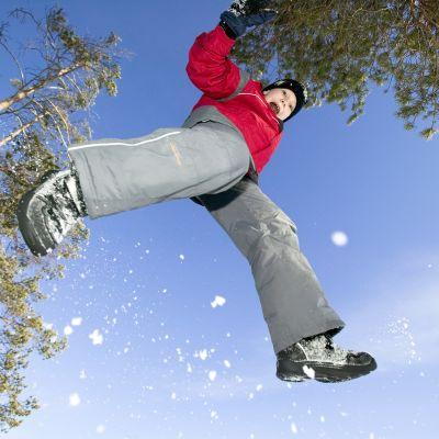 Poika hyppää talvisessa  metsässä.