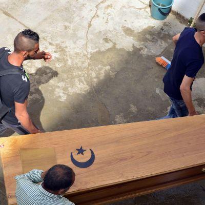 Tunisialaismiehet kantavat veneturmassa kuolleen sukulaisensa arkkua Sfaxissa.