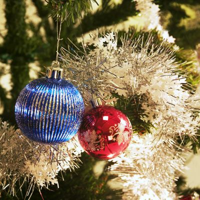 Joulukuusen koristeita sekä kynttilä joulukuusen oksilla.