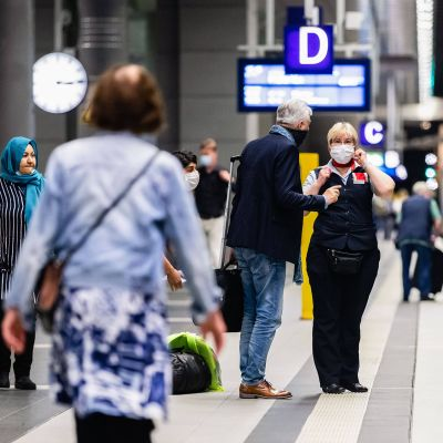 Junahenkilöstö neuvoo matkustajia Berliinin keskusrautatieasemalla.