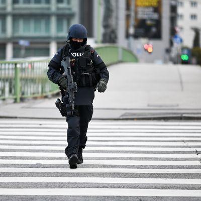 Aseistettu poliisi kävelee kadulla Wienissä.