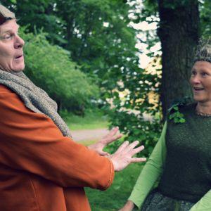 Yngve Källberg och Vivi-Anna Rehnström agerar mot varandra i sina teaterkläder i en grön park.