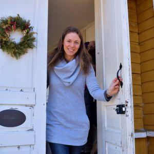 Hanna Vuorio-Wilson tittar ut genom en vit gammal dörr i ett gult trähus.