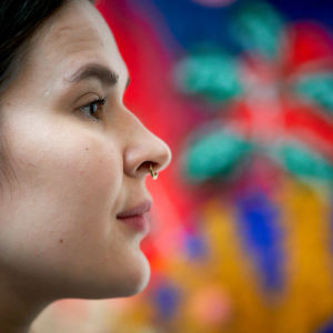 En ung kvinnas ansikte i profil mot bakgrund av en målning.