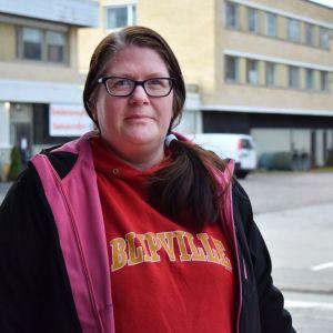 Ulrika Malm, en medelålders kvinna med svarta glasögon och röd tröja invid torget i Dalsbruk.