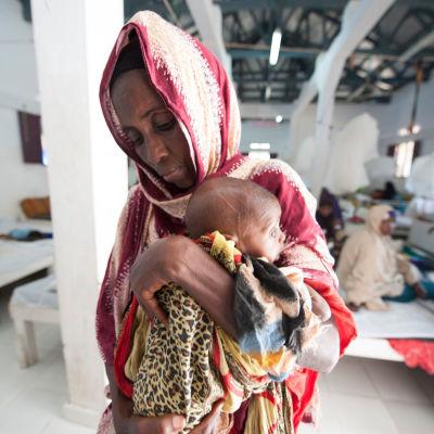 En mormor med sitt udnernärda barnbarn på Kismayo General Hospital's Stabilization Centre