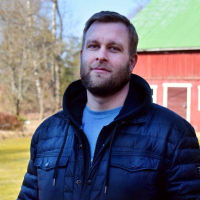 Mikko Pihlström står ute en solig vårdag, ett rött träskjul i bakgrunden.