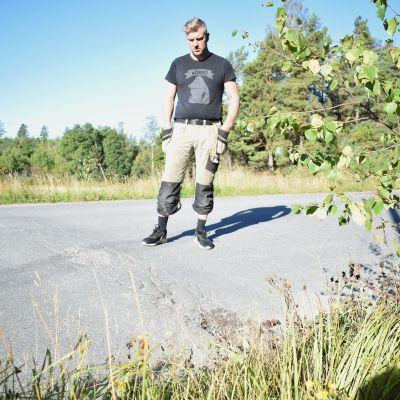 Andreas Ölander intill vägguppen som gör att bilarna kör mitt på vägen i den branta kurvan.