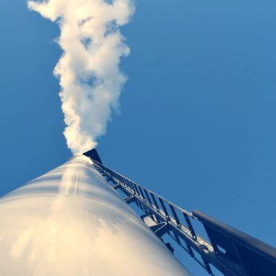 En skorsten som sträcker sig högt upp i luften, ut kommer vit rök, förmodligen vattenkondens.