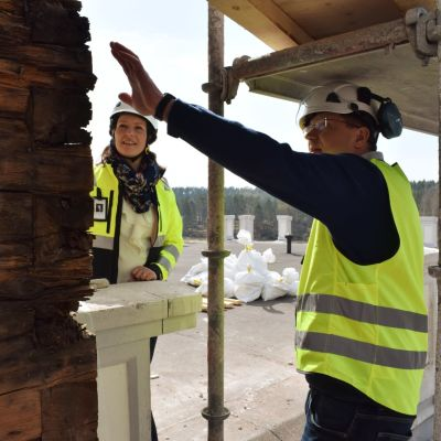 Mikaela Pappila och Mikael Jensen på en byggnadsställning i gula västar.
