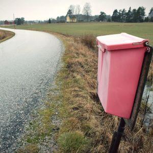 En röd postlåda vid en enslig väg. Ett trähus intill åkerkanten i bakgrunden.