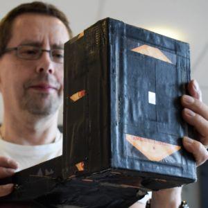 Hans G Hästbacka håller upp en nålhålskamera, en svarttejpad låda, stor som en större bok, framför sig.