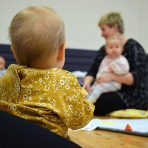 En baby, fotad bakifrån, sitter i famnen på sin mamma och ser mot en annan mamma med baby längre bort.