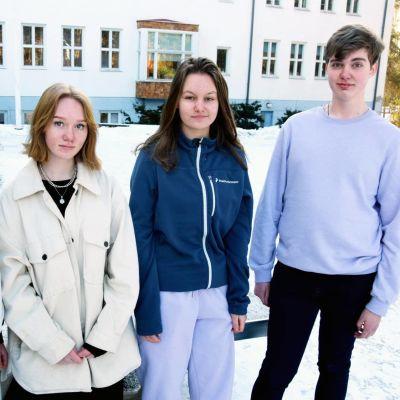 Fyra ungdomar framför en skola