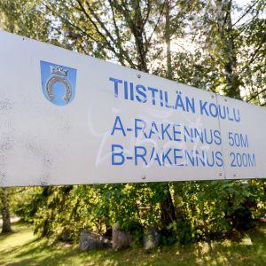 Skylt med texten Tiistilän koulu, skolan i Distby