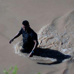 Mies kahlaa tulvavedessä maantiellä Hondurasissa.