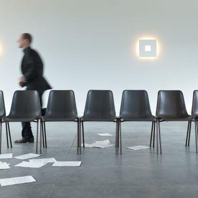 Mies juoksee tyhjän tuolirivin takana ja lattialla on papereita.
