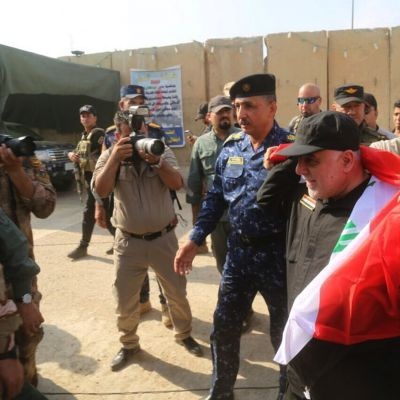 Pääministeri lippu harteillaan sotilaiden ja median ympäröimänä.
