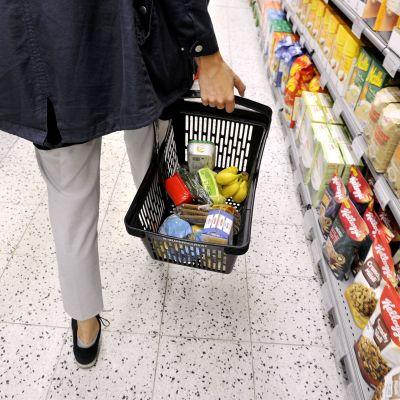 Nainen kantaa kauppakoria ruokakaupassa.