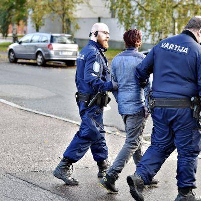 Poliisit vievät miestä käsikynkässä Sirrikujalla Kontulassa Helsingissä perjantaina iltapäivällä 6. lokakuuta.