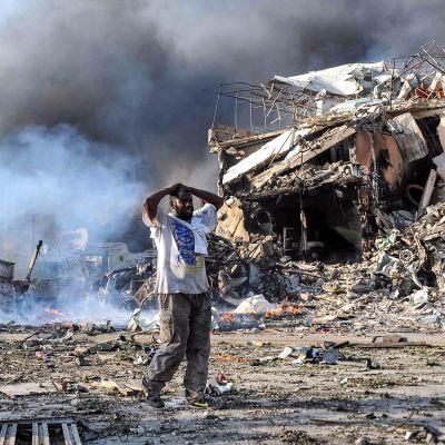 Mies katselee pommi-iskun tuhoja Mogadishussa lauantaina.